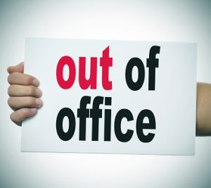 man hand and arm holding a signboard with the text out of office written in it